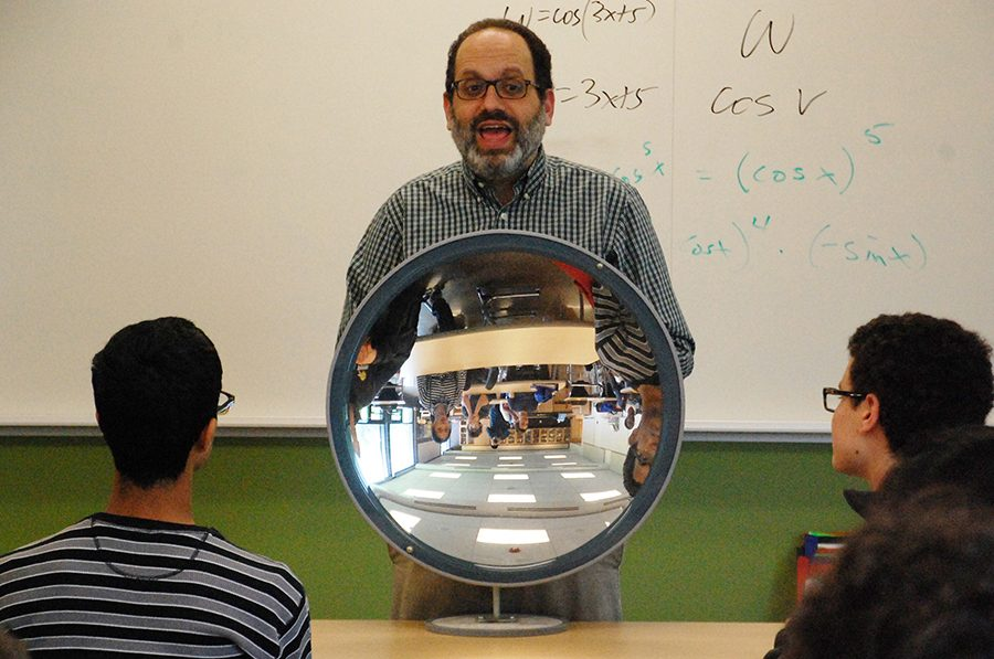 """Physics teacher Michael Lerner demonstrates properties of light, holding a concave mirror up to his class and asking students, """"what do you see?"""" Photo by Yuke Zheng"""