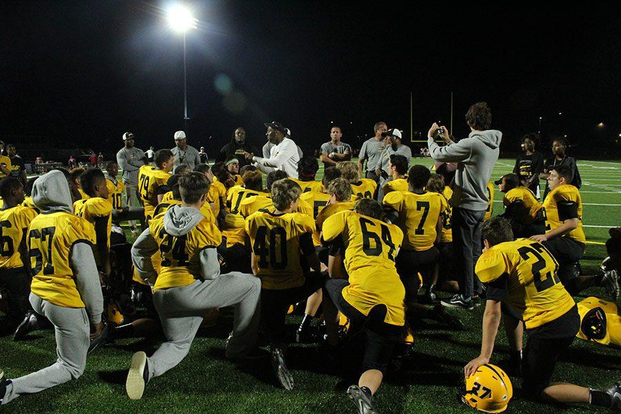 The Bison huddle at the Perry game on Sept. 9. Photo by Gabriela Colovan Costa.