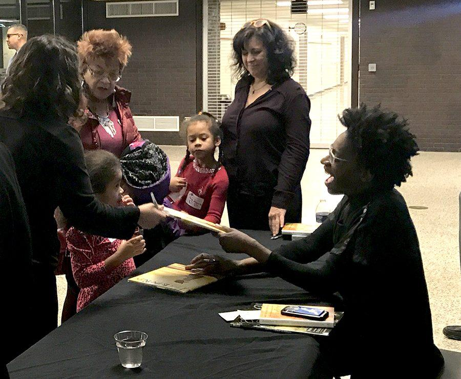At+the+end+of+the+evening%2C+Jacqueline+Woodson+sat+at+her+own+table+signing+books+while+audience+members+enjoyed+cookies+and+drinks+that+had+been+set+up+outside+of+the+auditorium.+Photo+by+Malinda+Creel.