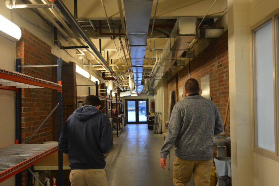 A hallway runs underneath the cafeteria with a room to the right that used to be the woodshop. To the left are shelves piled high with custodial products and boxes of supplies. Photo by Nicole Breger