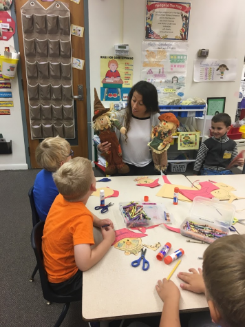 Mayfield High School senior Emmie Rotsky works on fall crafts with a group of elementary students.