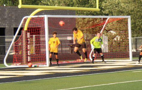 Senior Daniel Uria heads the ball, preventing a Lutheran West shot on goal against senior captain Jake Muencz